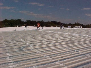 Cool white roof after flashing and as the first coat is applied by Roof Menders