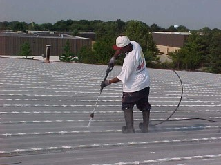 Pressure washing by Roof Menders' crew member