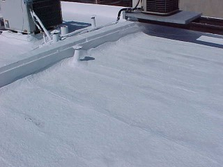 White acrylic roof coating over foam roof by Roof Menders